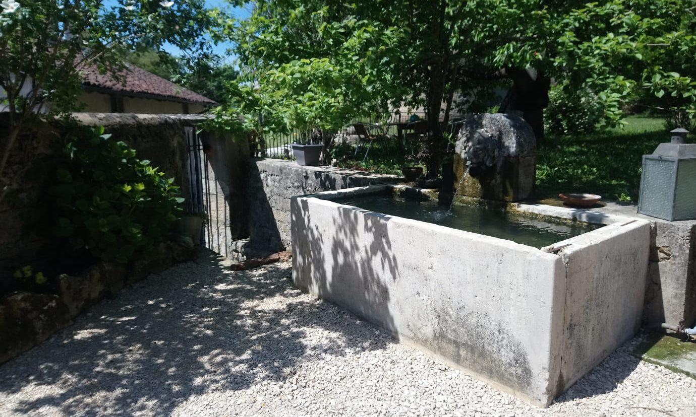 la fontaine et son jardin arboré, entouré de remparts